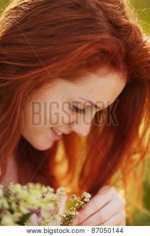 Freckled Red-haired Girl With A Bouquet