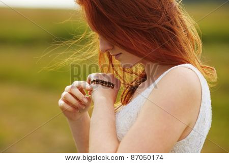 Big caterpillar crawling on the hands of a woman