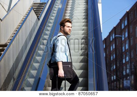 Young Guy With Bags Walking Up Escalator