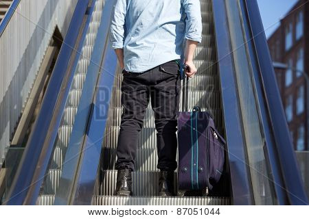 Young Man Standing On Escalator With Bag