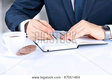 The Business Man Writing In The  Notebook. A Cup Of  Of Coffee With Cookies Behind