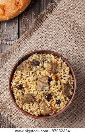 Pilaf is spicy indian food cooked with lot of rice, fried meat, carrot, onion and garlic