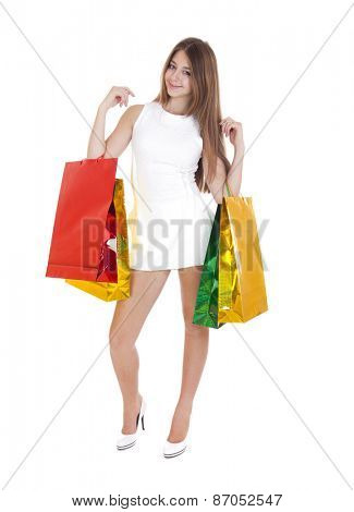 Full portrait of smiling young blonde girl with colorful shopping bags in white dress posing on a white background