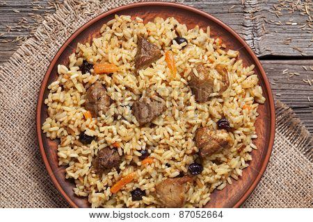 Dish of pilaf, national uzbek spicy meal with meat, rice, onion and garlic
