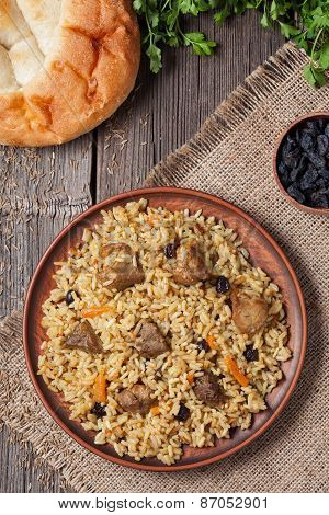 Plate of pilaf, traditional turkish spicy food with rice, fried meat, carrot onion and parsley