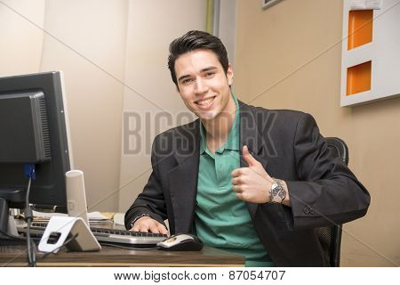 Smiling handsome young businessman sitting in the office