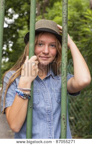 Young girl standing behind the bars of the old park.