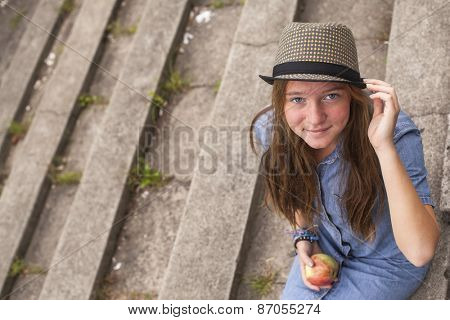 Young girl sitting on the stone steps of the old park.