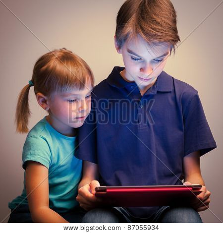 Children wearing casual clothes playing or watching a movie on a touch pad at home. Boy and girl are half-siblings. Brother is holding tablet with red cover.