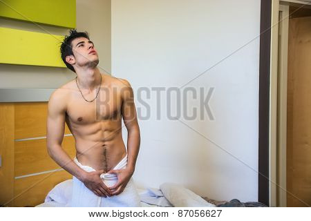 Young Shirtless Man Covered With Towel at Home in His Bedroom