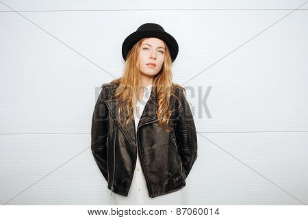Young beautiful fashionable woman in hat, leather jacket and white blouse posing outdoors against ga