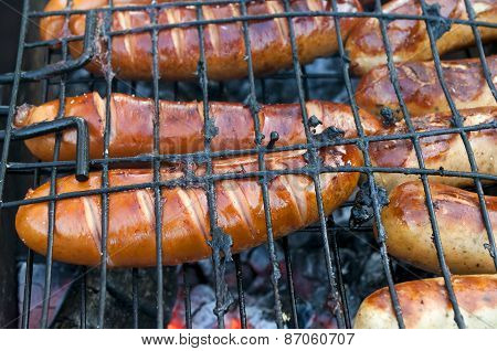 Barbecue With Fiery Sausages On The Grill