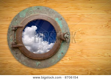 Antique Porthole On Bamboo Wall With View Of Blue Sky And Clouds