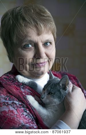 Beautiful elegant elderly lady with a cat at home