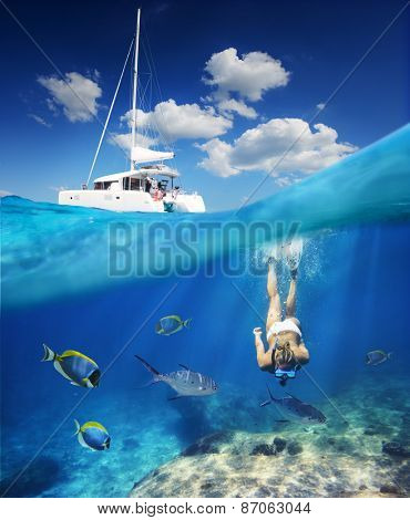 Girl diving in ocean with fishes next to catamaran at sunny day.