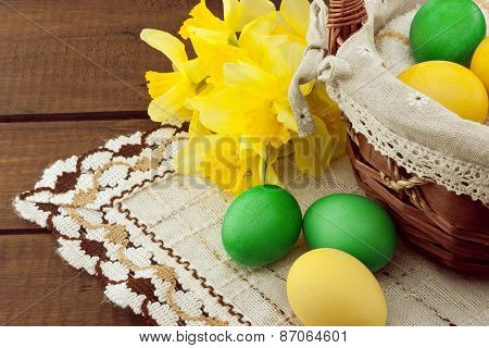 Easter Eggs In The Basket On Wooden Table With Bouquet Of Yellow Lent Lily Daffodil Or Narcissus