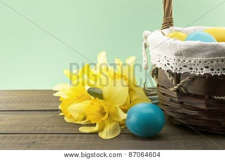 Easter Eggs In The Basket On Wooden Table With Bouquet Of Yellow Lent Lily Daffodil Or Narcissus, Gr