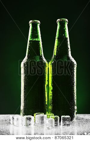 Glass bottles of beer with ice cubes on dark green background