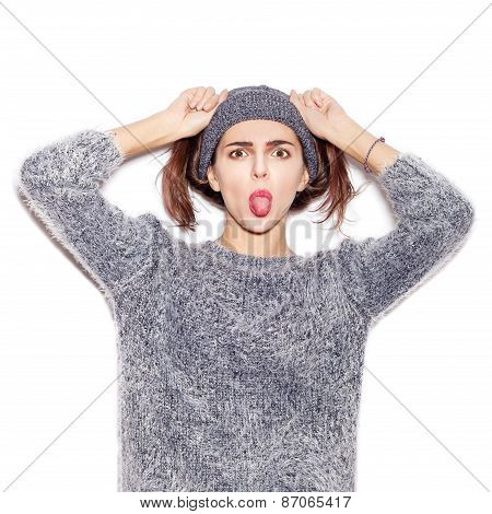Funky Girl In Knit Sweater And Hat  Showing Tongue