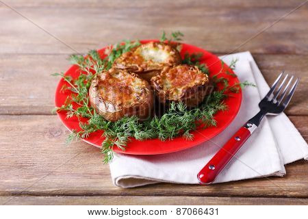 Baked potatoes with dill on pate on wooden table