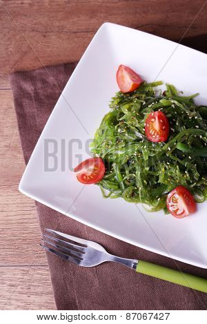 Seaweed salad with slices of cherry tomato in plate on napkin and wooden table background
