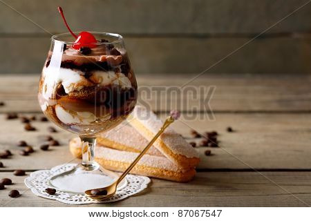 Tasty tiramisu dessert in glass, on wooden background