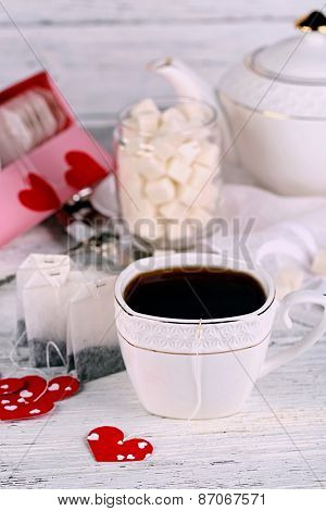 Heart shaped teabag tags, box and teacup on wooden background
