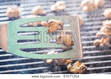Grilled champignon mushrooms on spatula with steam and drops of water