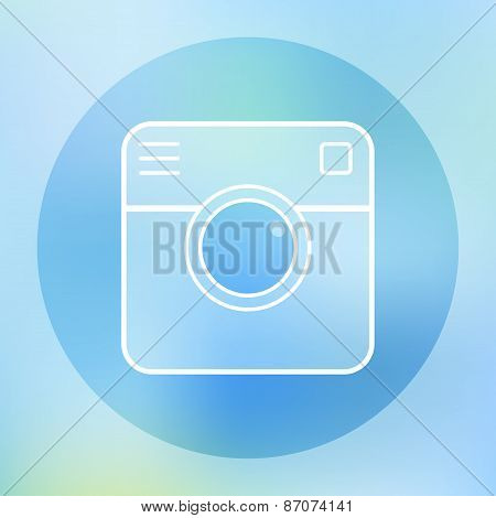 Camera transparent icon on blurred pink background.