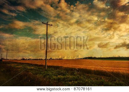 Vintage textured landscape with telephone lines along wheat fields in rural Prince Edward Island.