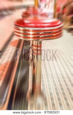 Red vinyl stools in a vintage diner. Motion blurred effect