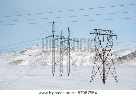 Electric cables and pylon towers on the snow covered land during winter