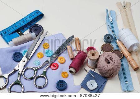 Sewing kit with scissors spools of thread and needles on white wooden background.