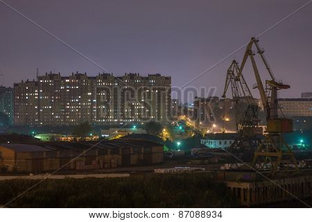 Industrial area with river port. Behind the houses