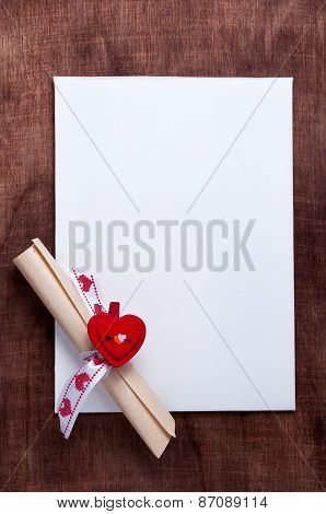 Valentine's day. White card with a small red heart on wooden backgrounda scroll of paper with wishes