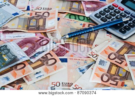 Pen And Calculator On A Pile Of Euro Banknotes