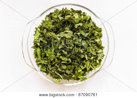 Chopped water spinach kept in a glass bowl on a plain background