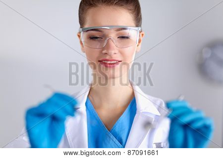 Attractive female dentist with tools , standing on gray