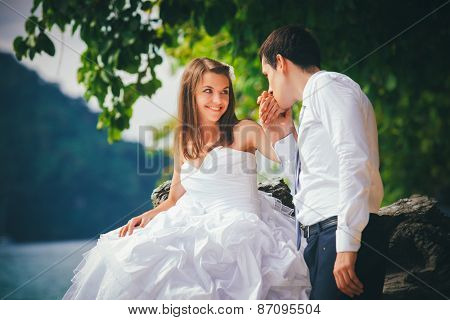 Young Bride Sits On Rock And Groom Kisses Hand