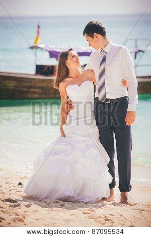 Bride And Groom Embrace Standing On Sand Beach