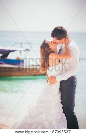 Bride And Groom Kiss Standing On Sand Beach