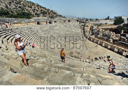 Ancient Amphitheater, Tourists Take Photos Themselves On Background Of Attractions.