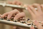 stock photo of flute  - Detail of female fingers on flute keys with second flute blurred on pastel backgournd - JPG