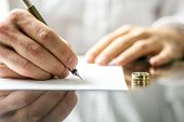 image of divorce-papers  - Closeup of a man signing divorce papers - JPG