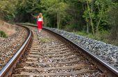stock photo of girl walking away  - Girl Walking On Rails in the Czech Republic - JPG