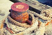 stock photo of bollard  - Old rusted mooring bollard with naval ropes on concrete pier vintage toned photo with old style filter effect - JPG