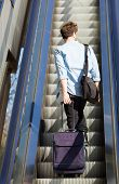 pic of escalator  - Young travel man standing on escalator with bags - JPG