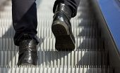 stock photo of escalator  - Low angle male feet walking in boots up escalator - JPG