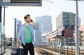 foto of people talking phone  - Portrait of a happy young man talking on mobile phone at train station platform