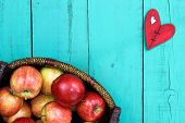 image of broken heart flower  - Wicker basket full of gala apples on antique teal blue wooden background with red wood country broken heart - JPG